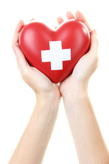 Red heart with cross sign in female hand, close-up, isolated