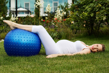 Beautiful pregnant woman relaxing in the park