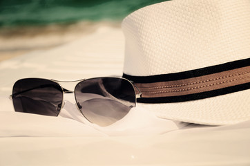 toned image white hat and sunglasses on the background of sea an