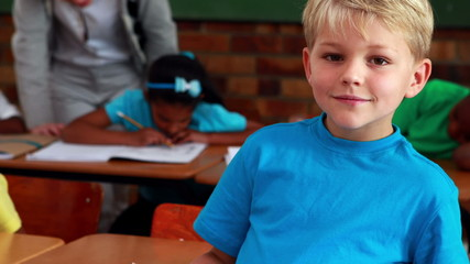 Little boy smiling at camera during class
