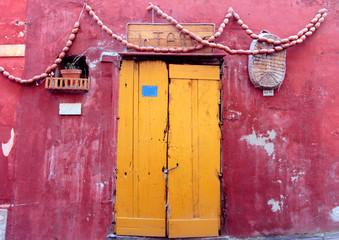 Una porta gialla su sfondo rosso a Procida