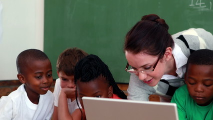 Pupils and teacher looking at laptop in classroom