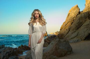 Lady in white dress on seashore