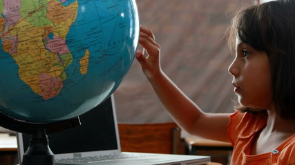 Little girl looking at globe in classroom