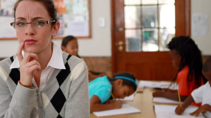Thoughtful teacher looking at camera at top of classroom