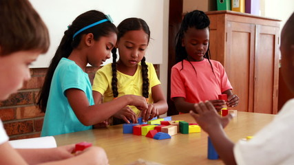 Pupils playing with building blocks in classroom