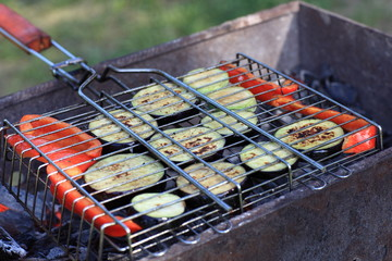 Slices of vegetable marrow and pepper on barbecue grill