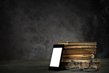 Smartphone (self-designed), old books and reading glasses