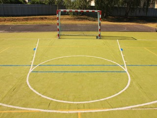 Empty outdoor hanball playground, plastic green surface, bounds