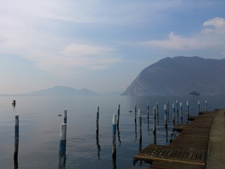 Pontile libero tra acqua, monti e cielo