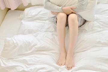 ベッドの上でゆったり過ごす女性