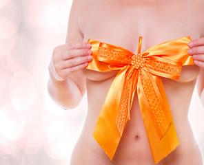 junge Frau hält sich eine Geschenkschleife vor die Brust