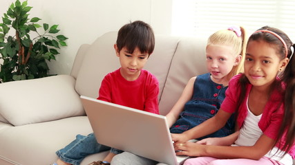 Three cute children using laptop together on the sofa