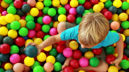 Cute boy playing and having fun in the ball pool