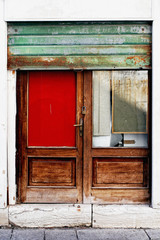 A wooden door in Venice with a red glass and a rusty green gate