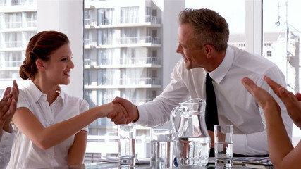 Manager shaking hands with employee with everyone clapping
