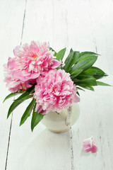 Pink peonies in retro vase on wooden table, vintage colors, tone