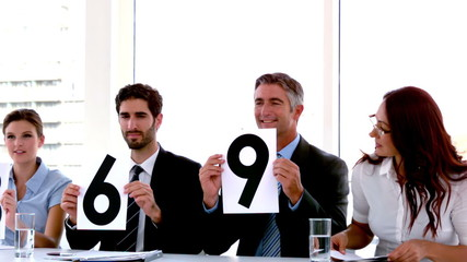 Business people on interview panel showing scores