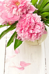 Pink peonies in retro vase on wooden table, closeup shot