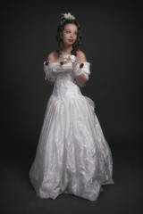 Victorian fashion woman wearing white dress. Holding porcelain t