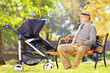 Grandfather sitting and looking at his baby nephew in a stroller