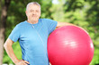 Mature sporty man holding a fitness ball in park