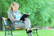 Mature woman reading a book in park seated on bench