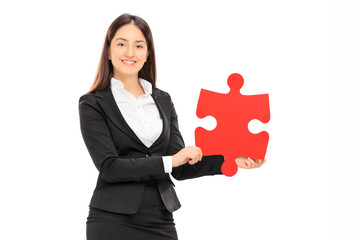 Businesswoman holding a piece of a puzzle