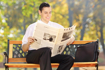 Businessman seated on a bench reading a newspaper in park