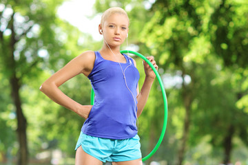 Female athlete on a mat holding a hula hoop in park