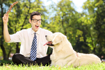 Guy seated on a grass playing with labrador retriver dog in a pa