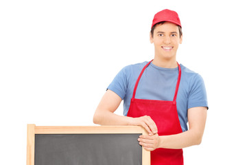 Man in apron standing behind a wooden blackboard