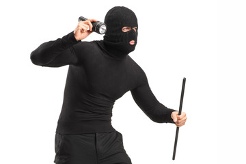 Robber with mask holding a flashlight and piece of pipe