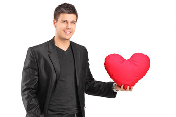 Romantic young man holding a heart