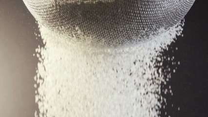 Flour falling through a metal sieve