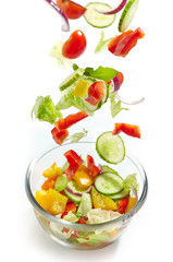 Fresh vegetables falling into the glass bowl