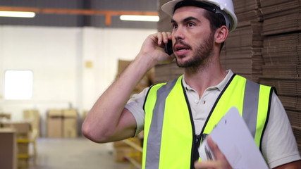 Warehouse worker talking on the phone holding clipboard