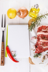 Cooking concept. Recipe book and ingredients for cooking meat
