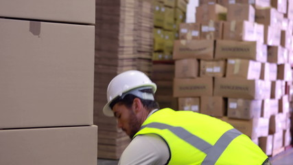 Warehouse worker packing up palette of boxes
