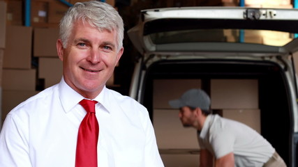 Delivery driver packing his van with manager smiling at camera