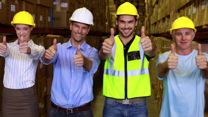 Warehouse team smiling and showing thumbs up together