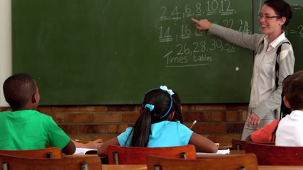 Young teacher teaching math to young class in classroom