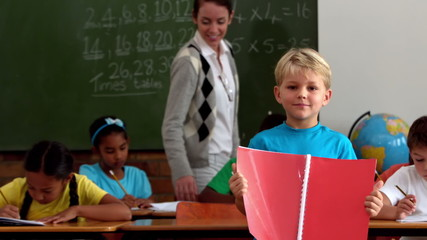 Little boy holding red notepad smiling at camera in classroom