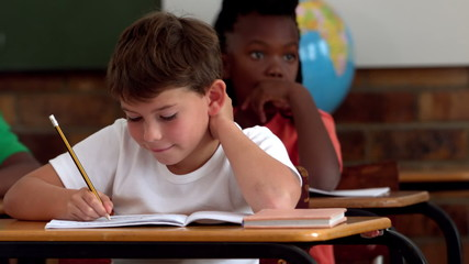 Little boy writing in notepad in classroom and smiling at camera