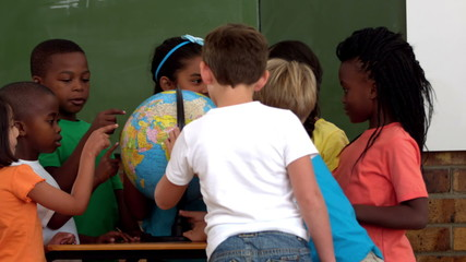 Cute pupils looking at the globe in classroom