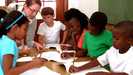 Teacher talking to her enthusiastic pupils writing in notepads