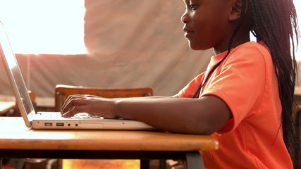 Little girl using laptop in classroom