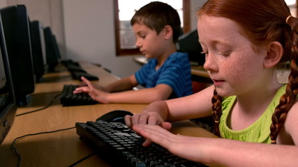 Little girl using computer in classroom in school