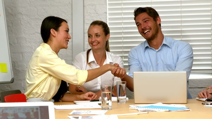 Casual business partners shaking hands during meeting