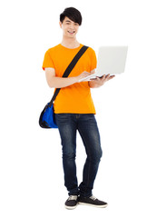 confident young student standing and using laptop